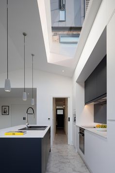 A modern kitchen with a skylight and pitched ceiling.