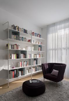 This modern sitting room features white open bookshelves and a comfortable armchair with matching footrest. #SittingRoom #Library #Shelving