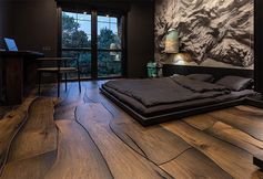 This modern bedroom features a unique wood floor made from 500-year-old oak, that fits together like puzzle pieces and showcases the natural grain, cracks, and knots. #UniqueWoodFloor #WidePlankFlooring #WoodFloor #FlooringIdeas #WoodFlooring
