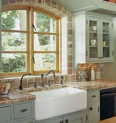 Farmhouse Sink Framed by Tumbled Marble- (Awesome look)- Rustic yet beautifully functional, this white farmhouse sink is set into a countertop and backsplash of tumbled marble. The arched window frame features recessed lighting to illuminate the work area day and night.
