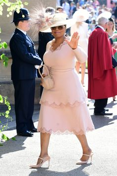 Oprah wears a blush, double tiered dress with lace trim made of sustainable viscose to the wedding of Prince Harry and Ms. Meghan Markle today in Windsor.