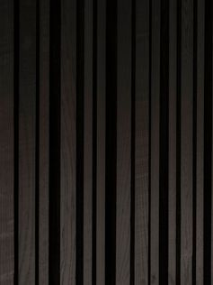 A matte black stained wood accent wall.