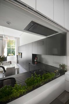 A window that doubles as a backsplash acts as a wall between the matte black kitchen and the bedroom.