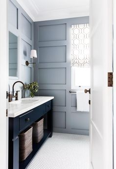 A navy blue vanity contrasts with the muted wall panelling painted in Resene 'Half Periglacial Blue'.