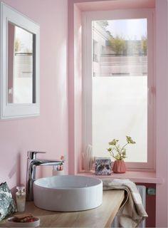 Une touche de glamour et d'originalité dans cette salle de bains entièrement repeinte en rose. Une  jolie vasque ronde posée sur un plan de travail en bois ajoute une note poétique à la pièce. / Castorama #salledebains #vasqueaposer #peinturerose #murrose #decorose #decoration