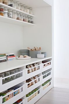 A modern white pantry with open shelves and drawers.