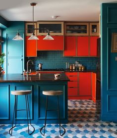 What an unexpected and deep colour combo: rer and teal in the kitchen. Cabaret floor tiles, firedearth.com.