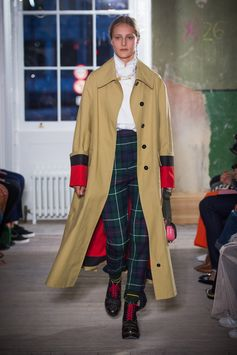 A bonded cotton car coat with a bright reverse is layered over a white herringbone cotton riding shirt and high-waisted green tartan stirrup trousers. The Pocket Satchel in pink completes the look.