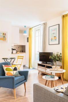 Salon coin canapé avec un grand mur jaune moutarde  dans Rénovation studio 25m2 . Idée décoration de salons Design et Contemporains sur Domozoom.