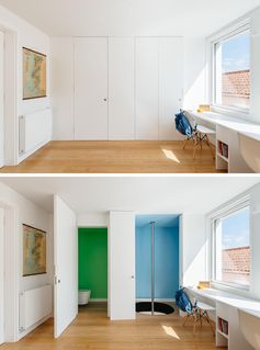 In the children's bedroom, two white doors are almost hidden within the wall. The first door opens to a bathroom with green walls, whereas the other door opens to reveal a mini blue room with a fire pole. #FirePole #KidsBedroom #FiremansPole #InteriorDesign