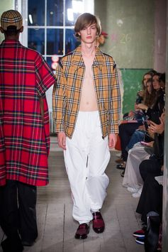 A street style look made up of a Vintage check Harrington jacket and white poplin track pants with contrast piping. Leather loafers with kiltie fringing finishes the look.