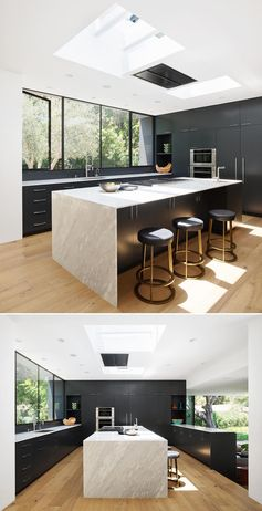 A modern kitchen with skylights, and Calcutta Cream marble countertops that contrast the matte black cabinets.