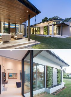 Sliding glass doors connect the interiors of this modern house with a covered outdoor space and the backyard. A rainwater chain adds a little decorative touch, and a water feature with plant walls and hidden lighting creates a focal point. #Backyard #YardIdeas #OutdoorLounge #WaterFeature #Landscaping