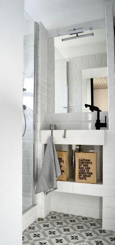 Une petite salle de bains blanche relevée de carreaux de ciment