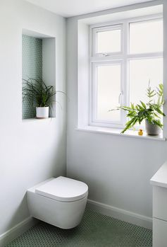 A Recessed Shelf Lined With Penny Tiles Adds A Pop Of Color To This Bathroom