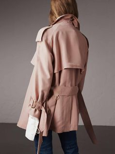 A silk trench coat characterised with an asymmetric wrap silhouette and oversize waterfall lapels and gunflaps for a light, fluid drape. The elegant design is finished with signature heritage details including elongated epaulettes. An elegant layer for your weekday wardrobe.