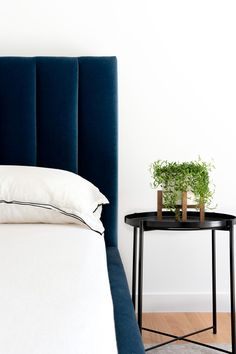 A bedroom with a deep, royal blue velvet headboard and bed frame, and a matte black side table with a small plant.