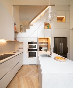 A white kitchen with recessed LED lighting.