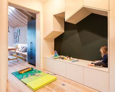Adjacent to the dining area int his updated home, is a small playroom with a built-in seating nook in the shape of a house, that's surrounded by storage cabinets. #BuiltInSeating #PlayRoom