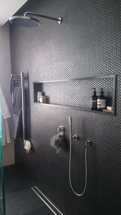 black penny tiles on the shower wall give it a textural look and add eye catchiness to the bathroom