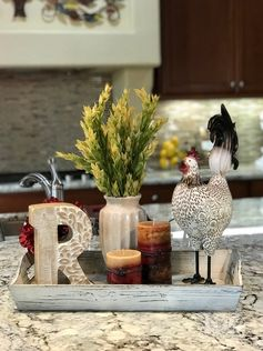 Tuscan kitchen island centerpiece I love this kitchen island centerpiece with a Tuscan theme. The rooster sits in a rustic white tray with Tuscan sunset colored candles and finished off with a vase with greenery and a large wooden letter.