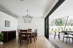A modern dining room with stacked sliding glass doors, white walls, and dark wood furniture.