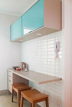 Decoração de apartamento colorido, na cozinha parede de tijolinho branco, armário azul, banco de madeira.
