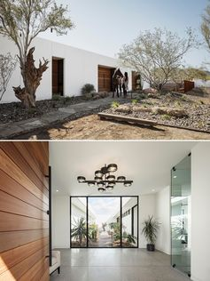 A modern white stucco house with a large wood front door that opens to a foyer with views of a courtyard.