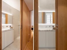 This small and narrow bathroom, which is located in a hallway that leads to the bedroom, has a wood pocket door that matches the wall. The first thing you see as you open the door is the bathroom vanity with a backlit mirror above it. #NarrowBathroom #BathroomDesign #ModernBathroom #SmallBathroom #PocketDoor