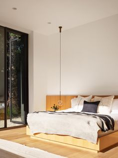A modern bedroom with a pendant light that acts as a bedside lamp.