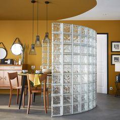 Cloison déco en briques de verre transparentes pour créer une alcôve tout en rondeur. Cette séparation en pavés de verre donne de l'intimité dans une pièce tout en préservant la lumière naturelle.  #murdeverre #briquedeverre #ideedeco #salon #cloison