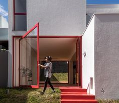 Nommo Arquitetos has recently completed the design of a house in Curitiba, Brazil, that showcases a large pivoting window next to the front door. #PivotingWindow #LargePivotWindow #RedFrontDoor #RedWindowFrames