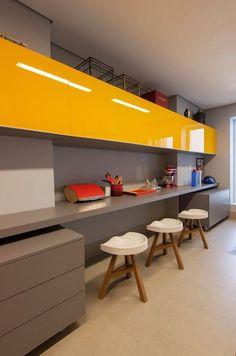 bureau suspendu en gris taupe, armoires hautes jaune laqué et tabourets design en bois massif