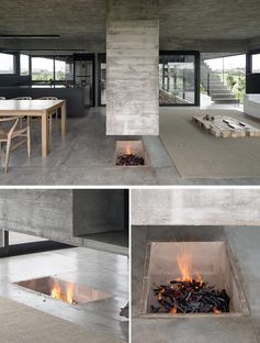 Designed as a sculptural element that separates the dining room and the living room, this modern hanging concrete divider has a chimney built into it on one end, and the other is a platform for holding the television. Underneath, the fireplace has been built into the ground. #Fireplace #RoomDivider #ConcreteDivider #HangingConcreteChimney #Concrete