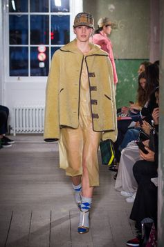 A spread-collar jacket in teddy bear shearling is worn over a soft-touch plastic hooded coat. A green and black tartan clutch is styled with gold high-heel sandals and blue knitted socks.