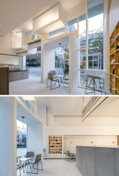 Inside this modern tea store, the high ceilings create a bright and open space, while the boxes shown on the facade of the store, penetrate through to the interior, creating a seating nook and a bar area. #TeaStore #TeaShop #CafeDesign #RetailDesign