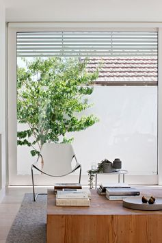 A modern living room with a wood coffee table and large windows.