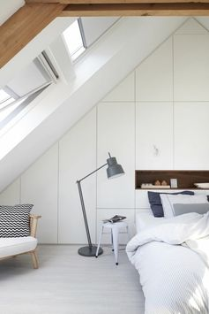 Chambre à coucher blanche avec fenêtre de toit