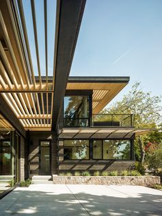 A modern house exterior with black-stained cedar siding and light wood sunscreens.