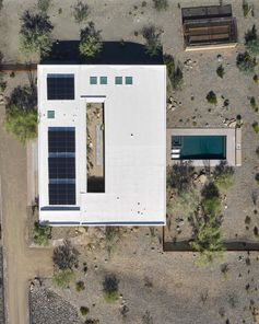 A modern house in the desert with a central courtyard, a swimming pool, and solar on the roof.