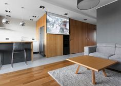 Instead of mounting a television in the living room, the designers of his modern apartment included a drop-down projector screen. #DropDownProjectorScreen #ProjectorScreen #InteriorDesign #LivingRoom