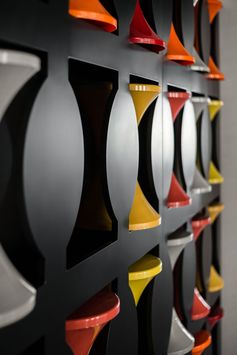 This modern office has a wall with cut-outs, that's dedicated to the storage of hourglass stools. When the stools aren't in use, they are placed into the empty spots in the wall, creating more room for walking around. #Stools #OfficeDesign #Workplace #WallStorage