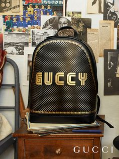 An homage to 80s video gaming culture, the Guccy print features SEGA's logo font—a fixture in the colorful arcades and coin-op game rooms of the time. The graphic font appears on a black leather backpack, combined with a stars and frame motif in a metallic gold print. The SEGA font is used with permission of SEGA Holdings Co., Ltd