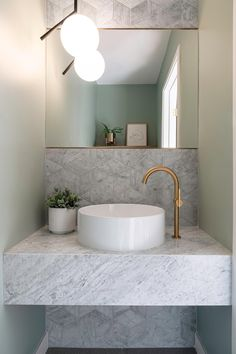 In this small but modern powder room, tile with a textural bamboo-like finish covers the wall, while a floating vanity is topped with a round white vessel sink and bronze accents.