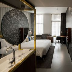 The open-plan guest rooms feature wall graphics by Jan Rothuizen, who created three hand-drawn maps that tell the story of the hotel and the surrounding area. Concrete Architects designed clever furniture pieces that multitask, including a sofa-desk hybrid and a vanity cabinet, to make the most of the available space.