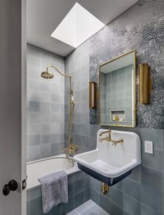 A bathroom with a floating vanity, gold hardware and faucet, and grey tiled walls and bathtub surround.