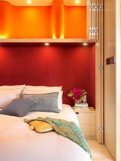 A dark red headboard sits below cabinets with an orange backdrop.