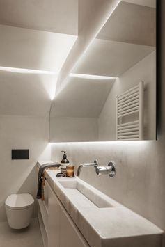 This small and narrow modern bathroom features a long thin vanity along one wall, with the shower at one end and the toilet at the other. Hidden lighting behind the mirror and in the shower niche help to keep the space bright. #SmallBathroom #NarrowBathroom #BathroomDesign #HiddenBathroomLighting