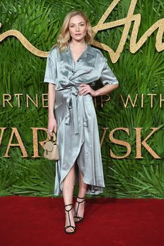 Wearing a satin tie waist dress, Clara Paget on the red carpet at the 2017 Fashion Awards in London