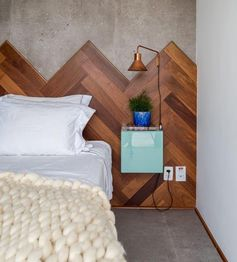 This modern wood headboard, with its different shades of wood laid in a herringbone pattern, travels the entire length wall, adding visual interest to the room, and softening the concrete wall and floor of the bedroom. #WoodHeadboard #Herringbone #ModernBedroom #HeadboardIdeas